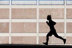 Physically fit man runs for exercise Stock Photos