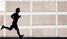 Physically fit man runs for exercise Stock Photo
