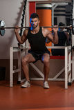 A Physically Fit Men Exercising By Doing Squats Royalty Free Stock Photos