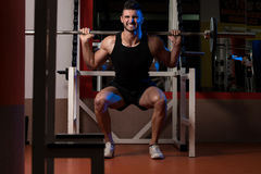 A Physically Fit Men Exercising By Doing Squats Royalty Free Stock Images