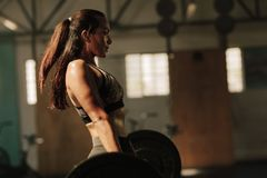 Physically fit woman lifting heavy weights. Fitness female doing heavy weight workout at gym Stock Photo