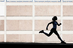 Physically fit woman runs for exercise Royalty Free Stock Photos