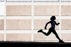 Physically fit woman runs for exercise Stock Photos