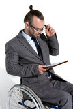 Physically handicapped businessman in wheelchair using digital tablet Stock Photography