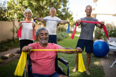 Physically impaired senior man holding ribbon with friends Stock Images