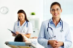 Physician. Portrait of confident female doctor looking at camera in hospital Stock Photos