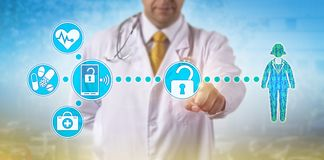 Physician Accessing Electronic Medical Records. Unrecognizable male physician is accessing electronic medical records of a female patient via secure wireless royalty free stock photo