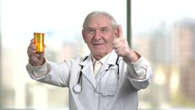 Physician is advising to use antidepressants. Old doctor in white coat and stethoscope consulting and recommed vitamins. Blurred city background out of window stock video