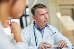 Physician as a senior physician with competence and responsibility. In a meeting in the clinic royalty free stock images