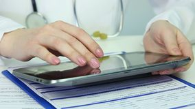 Physician browsing pages on tablet, consulting patients online, keeping records. Stock footage stock video footage