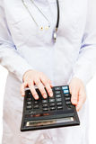 Physician calculates the cost of treatment. On calculator Stock Photography