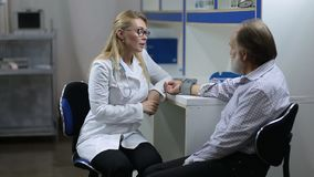 Physician checking male patient`s blood pressure stock video