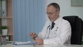 Physician checking patient medical form at hospital database, new technologies
