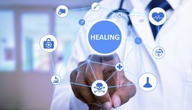 Physician choosing healing button among medical icons stock photos