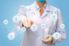 Physician clicks on the button with the question on the network . Physician clicks on the button with the question on the network with a blue background Stock Images