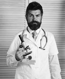 Physician with confused face ready to diagnose. Doctor in white medical coat holds microscope. Man in surgical uniform with stethoscope on neck on wooden stock photo