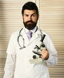Physician with confused face ready to diagnose. Doctor in white medical coat holds microscope. Man in surgical uniform with stethoscope on neck on wooden royalty free stock photos