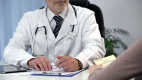 Physician consulting patient, writing symptoms, woman reading prescription royalty free stock photography