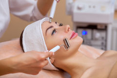 The physician-cosmetologist makes the apparatus a procedure of `galvanic` ultrasound cleaning of the face skin Royalty Free Stock Photos