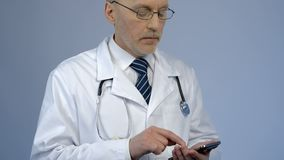 Physician dialing number or typing message on smartphone, online consultation stock images