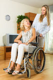 Physician and disabled female communicating. Friendly physician and positive disabled female on chair communicating indoor Stock Photo