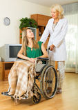 Physician and disabled girl communicating. Friendly physician and smiling disabled girl on chair communicating indoor Royalty Free Stock Photography