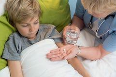 Physician giving boy medicine Royalty Free Stock Photos