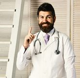 Physician with happy face ready to diagnose. Man in surgical uniform with stethoscope on neck on wooden background. Doctor in medical coat points finger up royalty free stock photos