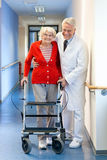 Physician helping a senior woman in a walker. Physician helping a senior women in a walker supporting her with an arms around her shoulders as he assists her Royalty Free Stock Images
