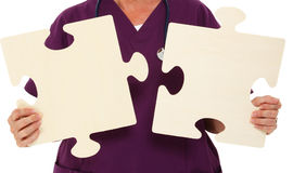 Physician Holding Puzzle Pieces. Over White Background Stock Photos