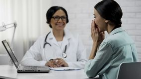 Physician informing patient about good news, showing test results on laptop. Stock photo royalty free stock photos
