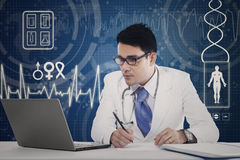 Physician with laptop making prescription Stock Photo
