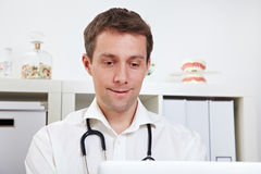 Physician with laptop in office. Physician working with his laptop in the doctor's office Royalty Free Stock Photos