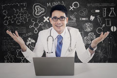 Physician with laptop and scribble Royalty Free Stock Photography
