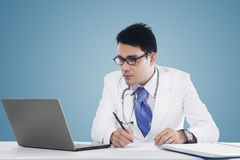 Physician makes prescription with notebook Stock Photography