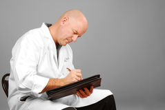 Physician Making Notes. Male doctor in white coat looking serious while making notes royalty free stock photography