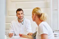 Physician measures blood pressure. In medical consultation royalty free stock image