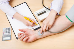 Physician measures blood pulse of patient Royalty Free Stock Photos