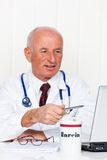 Physician in practice with stethoscope and laptop. Stock Photos