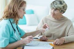 Physician prescribing medicament. Mature physician prescribing medicament for elder woman Royalty Free Stock Images