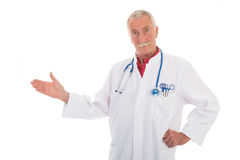 Physician presenting something on white background. Senior physician standing in studio on white background Royalty Free Stock Images