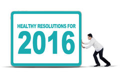 Physician pushing healthy resolutions for 2016. Photo of a male young doctor pushing a board with healthy resolutions for 2016, isolated on white Stock Image