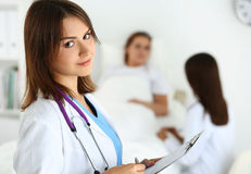 Physician ready to examine and help. Smiling female medicine doctor filling patient medical history list during ward round while patient communicating with Stock Image