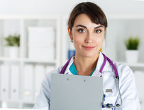 Physician reception concept. Beautiful female medicine doctors holding clipped document pad portrait. Medical help or insurance concept. Friendly smiling Stock Photos