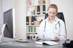 Physician Reviewing her Written Findings on Paper Stock Photos