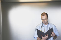 Physician Reviewing Notes In Elevator Royalty Free Stock Photography