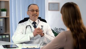 Physician satisfied with treatment result talking to female patient, recovery. Stock photo royalty free stock images