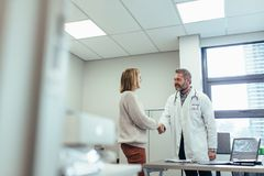 Physician shaking hands with patient in clinic. Male physician shaking hands with patient in clinic. Medical professional meeting women in hospital Stock Images