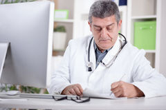 Physician with stethoscope around his neck working in office. Modern senior doctor  in the office Stock Photo