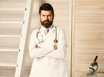 Physician with strict face ready to diagnose. Man in surgical uniform with stethoscope on neck on wooden background. Healthcare and treatment concept. Doctor royalty free stock image